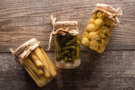 top view of delicious homemade tasty pickled cucumbers, corn and mushrooms on wooden rustic table