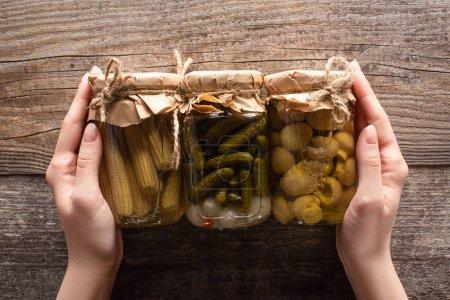 abgeschnittene Ansicht der Frau hält Gläser mit köstlichen hausgemachten schmackhaften eingelegten Gurken, Mais und Pilzen auf rustikalen Holztisch