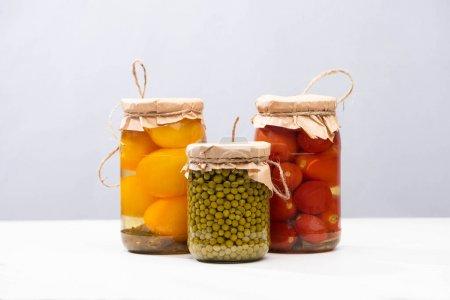 Photo pour Tomates marinées maison délicieuses et pois verts dans des bocaux isolés sur gris - image libre de droit