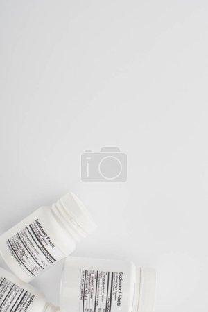 Photo pour Vue du dessus des récipients avec compléments alimentaires sur fond blanc - image libre de droit