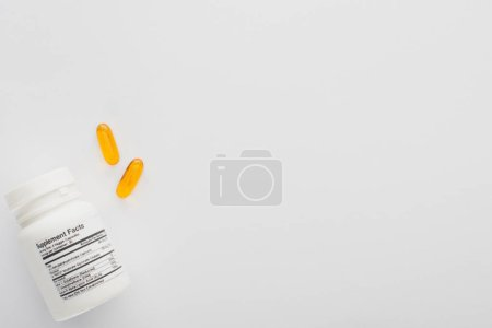 Photo for Top view of container and fish oil capsules on white background - Royalty Free Image