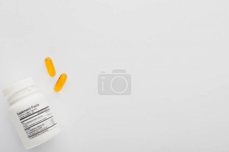 Top view of container and fish oil capsules on white background