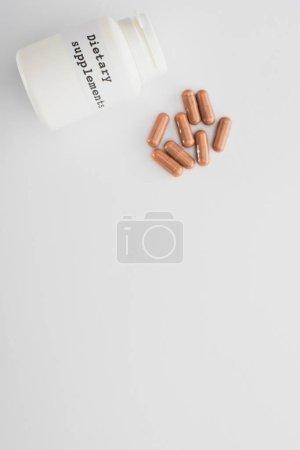 Photo pour Vue du dessus du récipient avec des compléments alimentaires lettrage et capsules brunes sur fond blanc - image libre de droit
