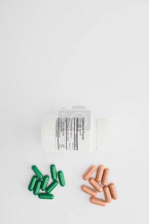 Photo pour Vue du dessus du récipient avec capsules brunes et vertes sur fond blanc - image libre de droit
