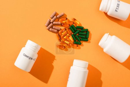 Photo for Top view of containers with omega-3 and fish oil lettering near capsules on orange background - Royalty Free Image