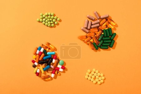 Top view of multicolored pills and capsules on orange background