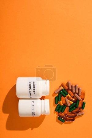 Photo pour Vue du dessus des récipients avec de l'huile de poisson et des suppléments alimentaires lettrage près de capsules colorées sur fond orange - image libre de droit