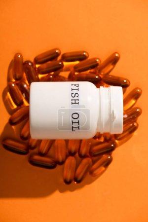 Photo pour Vue grand angle du récipient avec inscription à l'huile de poisson sur capsules sur fond orange - image libre de droit