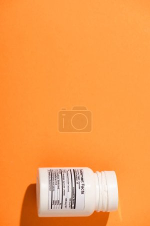 Photo for Top view of white container with dietary supplements on orange background - Royalty Free Image
