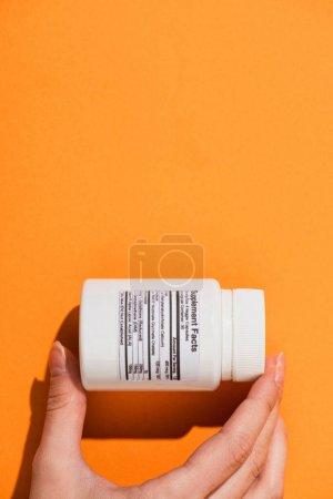 Photo pour Vue partielle de la femme tenant un récipient blanc avec des compléments alimentaires sur fond orange - image libre de droit