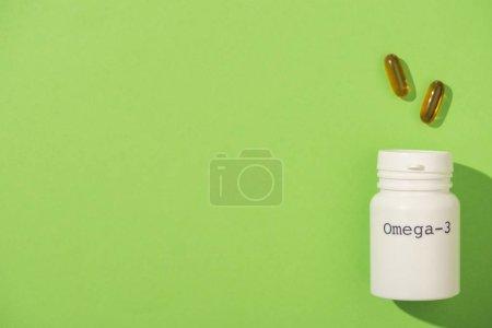Photo pour Vue du dessus du récipient avec lettrage oméga-3 près des capsules sur fond vert - image libre de droit