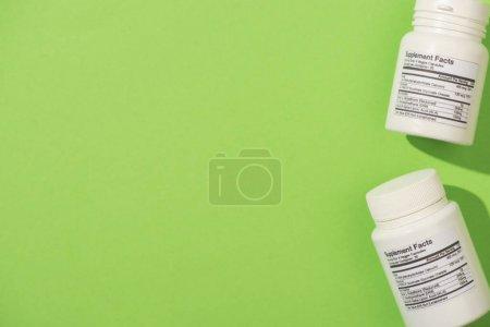 Photo pour Vue du dessus des récipients avec compléments alimentaires sur fond vert - image libre de droit