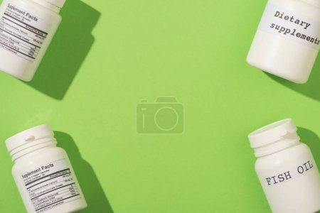 Top view of containers with fish oil and dietary supplements lettering on green background