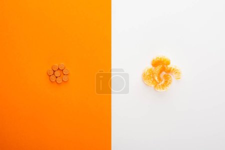 Photo for Top view of bright pills and mandarin on white and orange background - Royalty Free Image