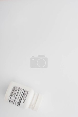 Photo for Top view of container with dietary supplements on white - Royalty Free Image