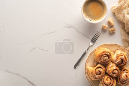 top view of fresh homemade cinnamon rolls on marble surface with cup of coffee, fork and cloth