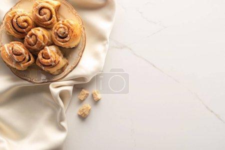Draufsicht auf frische hausgemachte Zimtrollen auf Seidentuch auf Marmoroberfläche mit braunem Zucker