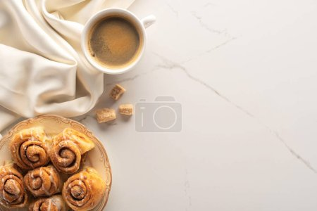 top view of fresh homemade cinnamon rolls on marble surface with cup of coffee, brown sugar and silk cloth