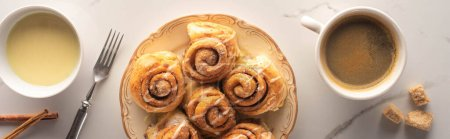 top view of fresh homemade cinnamon rolls on marble surface with cup of coffee, fork and condensed milk, panoramic shot
