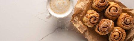 Draufsicht auf frische hausgemachte Zimtrollen auf Pergamentpapier auf Marmoroberfläche mit Tasse Kaffee, Panoramaaufnahme