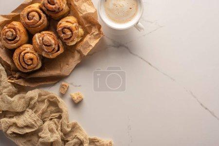 Foto de Vista superior de los rollos de canela casera frescos sobre papel de pergamino en la superficie de mármol con taza de café, azúcar marrón y tela. - Imagen libre de derechos
