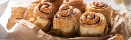 close up view of fresh homemade cinnamon rolls on parchment paper, panoramic shot