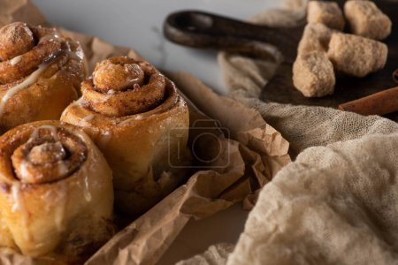 Photo for Close up view of fresh homemade cinnamon rolls near cloth and brown sugar - Royalty Free Image