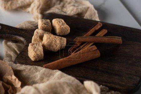 fresh cinnamon sticks and brown sugar on wooden cutting board near cloth