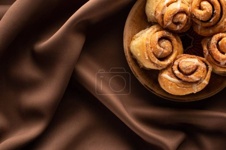 top view of fresh homemade cinnamon rolls on plate on silk brown cloth