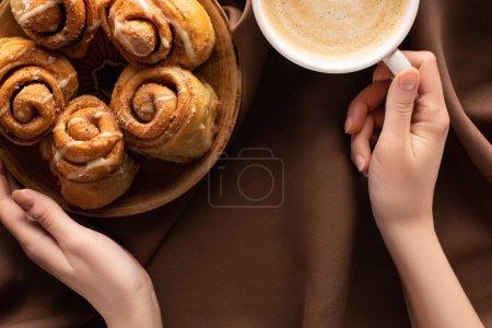 abgeschnittene Ansicht einer Frau, die einen Teller mit frischen hausgemachten Zimtröllchen in der Nähe von Kaffee auf seidenbraunem Tuch hält