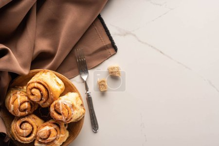 Photo for Top view of fresh homemade cinnamon rolls on marble surface with brown sugar, fork and brown silk cloth - Royalty Free Image