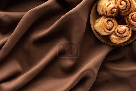 Photo pour Vue de dessus des rouleaux de cannelle maison fraîche sur tissu brun soie - image libre de droit