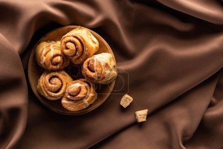 Draufsicht auf frische hausgemachte Zimtrollen auf seidenbraunem Tuch mit braunem Zucker