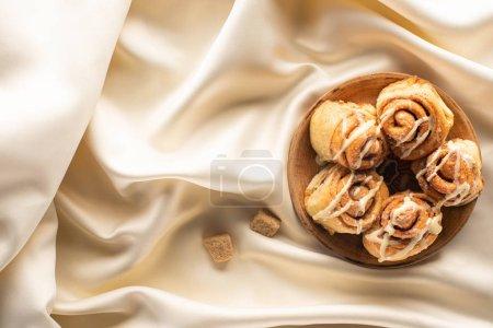 Draufsicht auf frische hausgemachte Zimtrollen auf seidenweißem Tuch mit braunem Zucker