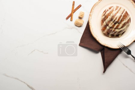 Photo for Top view of fresh homemade cinnamon roll on plate on marble surface with brown sugar, cinnamon sticks, napkin and fork - Royalty Free Image