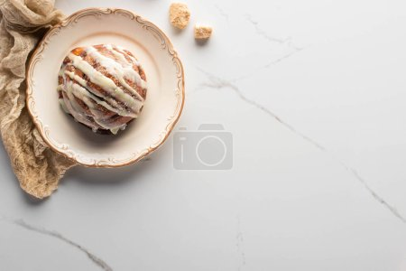 Photo for Top view of fresh homemade cinnamon roll on plate on marble surface with brown sugar and cloth - Royalty Free Image