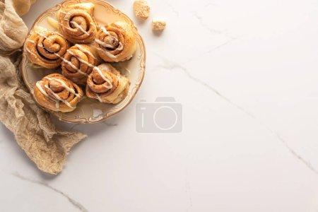 Foto de Vista superior de rollos de canela caseros frescos en la superficie de mármol con azúcar morena y tela - Imagen libre de derechos