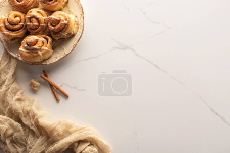 top view of fresh homemade cinnamon rolls on marble surface with brown sugar, cinnamon sticks and cloth