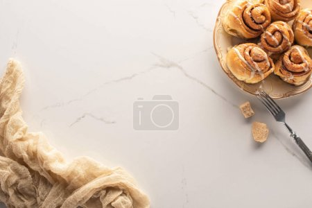 Photo for Top view of fresh homemade cinnamon rolls on marble surface with brown sugar, fork and cloth - Royalty Free Image