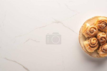 Draufsicht auf frische hausgemachte Zimtrollen auf Marmoroberfläche