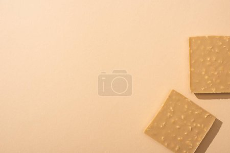 top view of delicious broken white chocolate bar on beige background