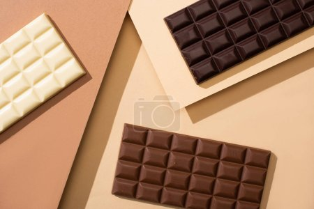 Photo for Top view of delicious white, milk and dark chocolate bars on beige background - Royalty Free Image