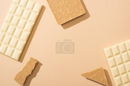 top view of delicious broken and whole white chocolate bars on beige background