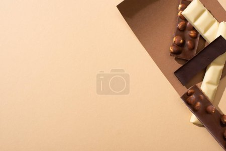 Photo for Top view of delicious dark, white and milk chocolate with nuts on paper on beige background - Royalty Free Image