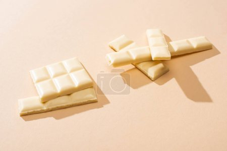 Photo for Sweet delicious broken white chocolate bar on beige background - Royalty Free Image