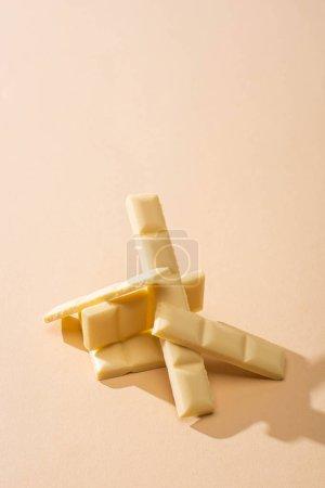 sweet delicious broken white chocolate bar on beige background