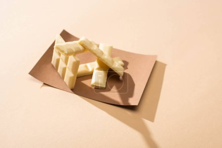 sweet delicious broken white chocolate bar on paper on beige background