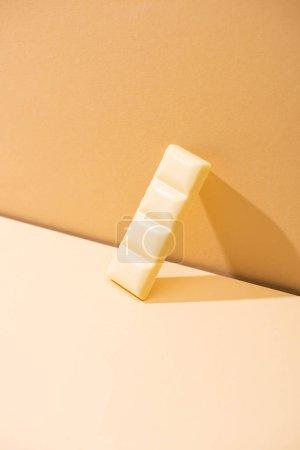 süße köstliche gebrochene weiße Schokolade Stück auf beigem Hintergrund