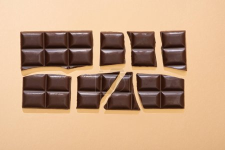 Photo for Top view of delicious broken dark chocolate bar on beige background - Royalty Free Image