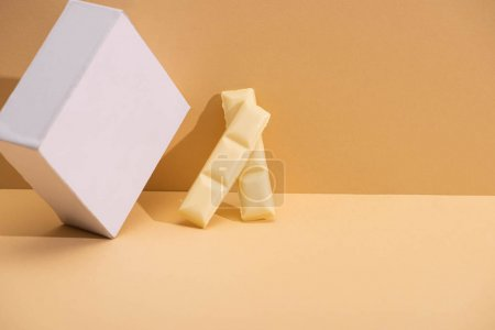 delicious white chocolate pieces and cube on beige background